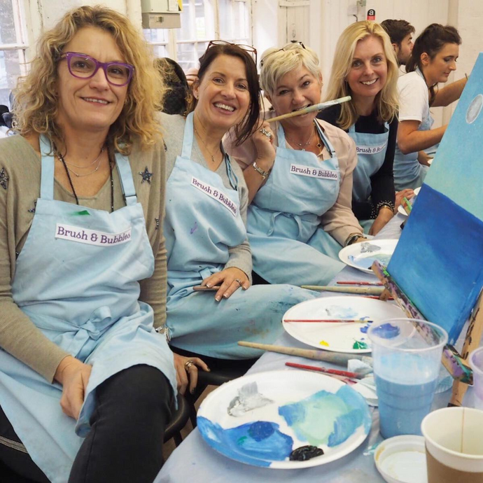 Women smiling during the painting class in Brush and Bubbles aprons