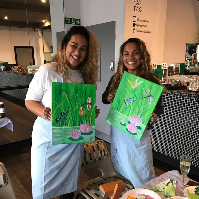Friends smiling whilst holding their beautiful canvas paintings