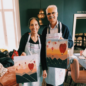 An older couple posing with their Cappadocia Hot Air Balloon paintings