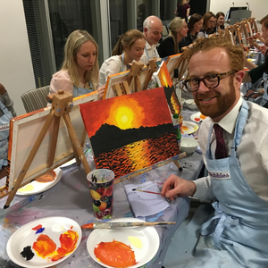 Employee posing with his sunset seaside canvas painting