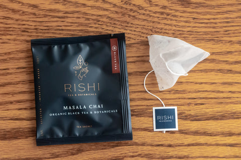 Rishi Masala Chai tea bag next to tea sachet.
