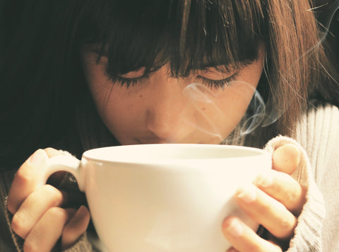 Woman inhaling cup of tea with eyes closed.