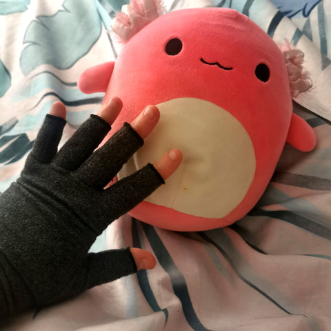 Sharon's hand in a grey compression glove, on top of their Archie the Axolotl Squishmallow
