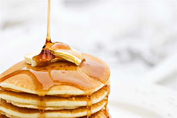 Maple Syrup poured over stack of pancakes