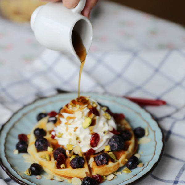 Maple Syrup pouring over waffles with berries and whipped cream