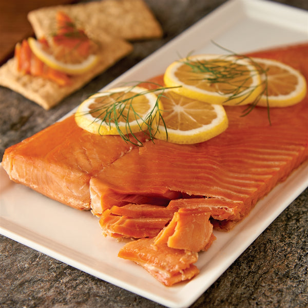 Wholeside of Wild Pink Smoked Salmon Retort on a plate with sliced lemons and dill