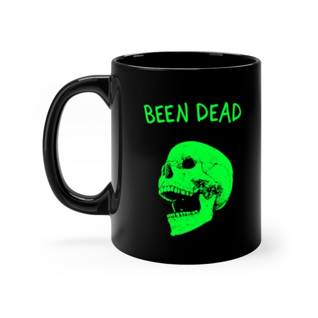 11 ounce black ceramic mug with been dead printed in spooky halloween neon green font on right side with laughing green skull below