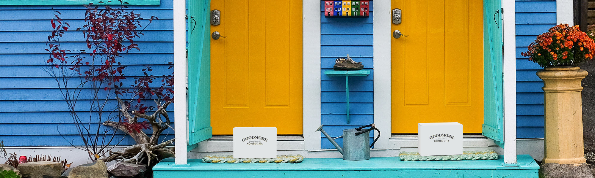 A delivery box of Goodmore Kombucha sitting on the doormat outside each of two side-by-side front doors.