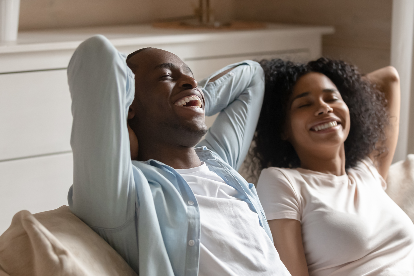 Black couple on a couch comfortably relaxed and smiling. Elevate For Him contributes to increased confidence and energy.