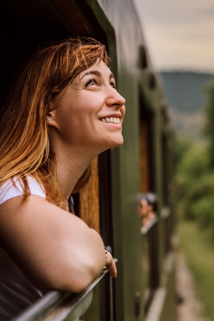 Woman looking out a train window at the greenery
