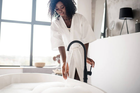 Woman pouring herself a bath to unwind