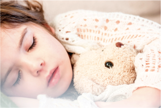 Image of child sleeping clutching a teddy bear