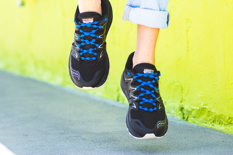 Jumping in front of green wall with black sneakers and tropical blue no tie shoelaces