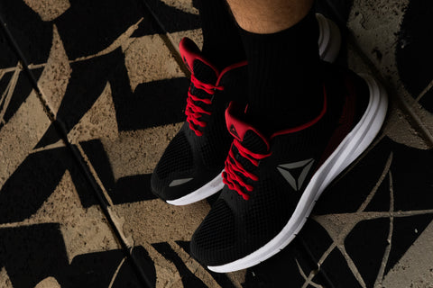 Red shoelaces on black sneakers