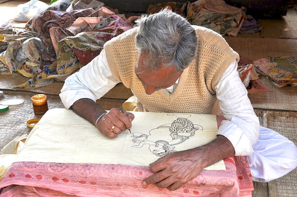 Indian man bent over fabric kalamkari technique