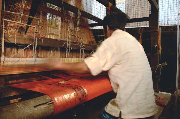Indian man weaving on handloom orange gold fabric