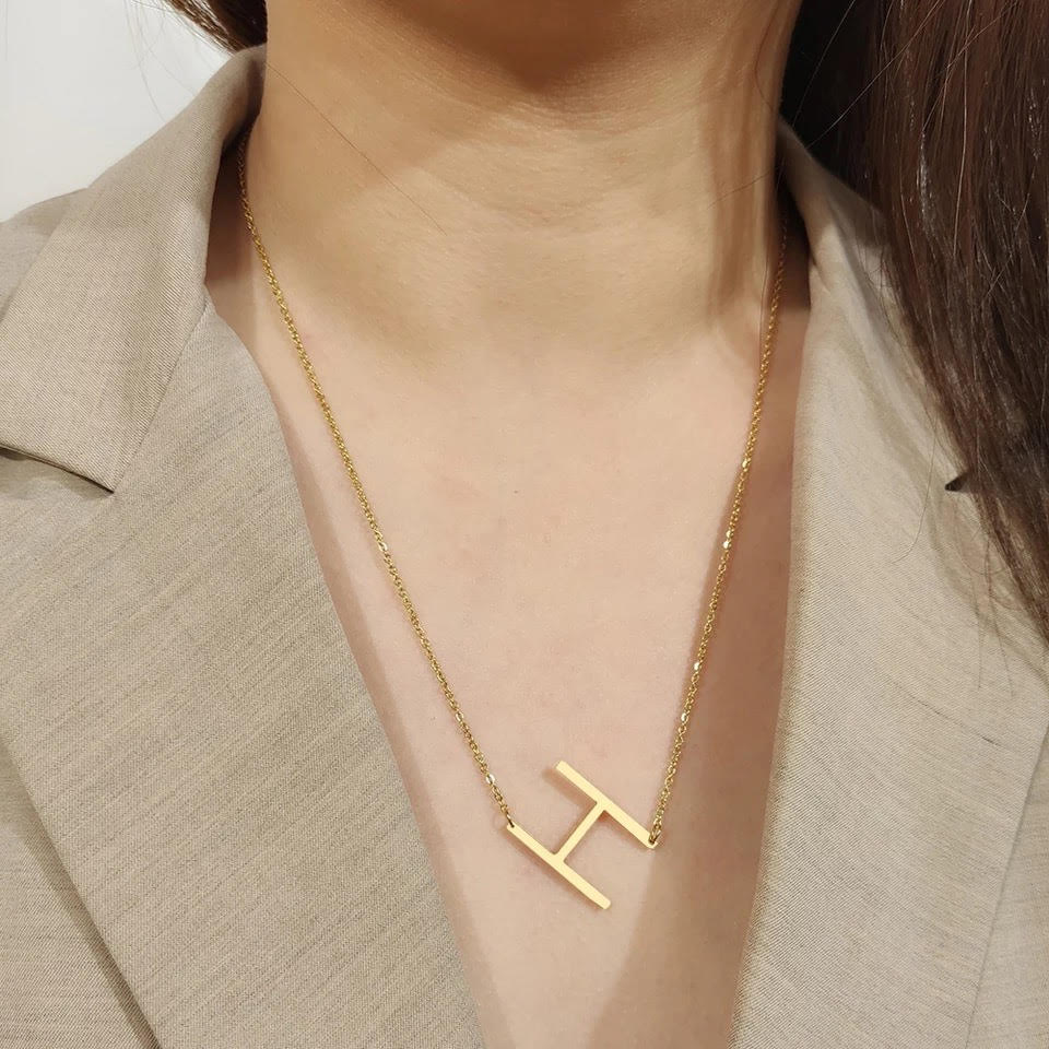 Gold initial pendant necklace worn by an Asian woman with a beige collar dress shirt