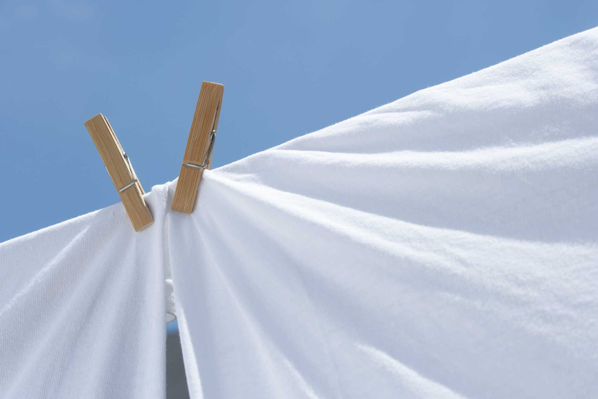 close up of white sheets drying in the sun on a line with clothes pins