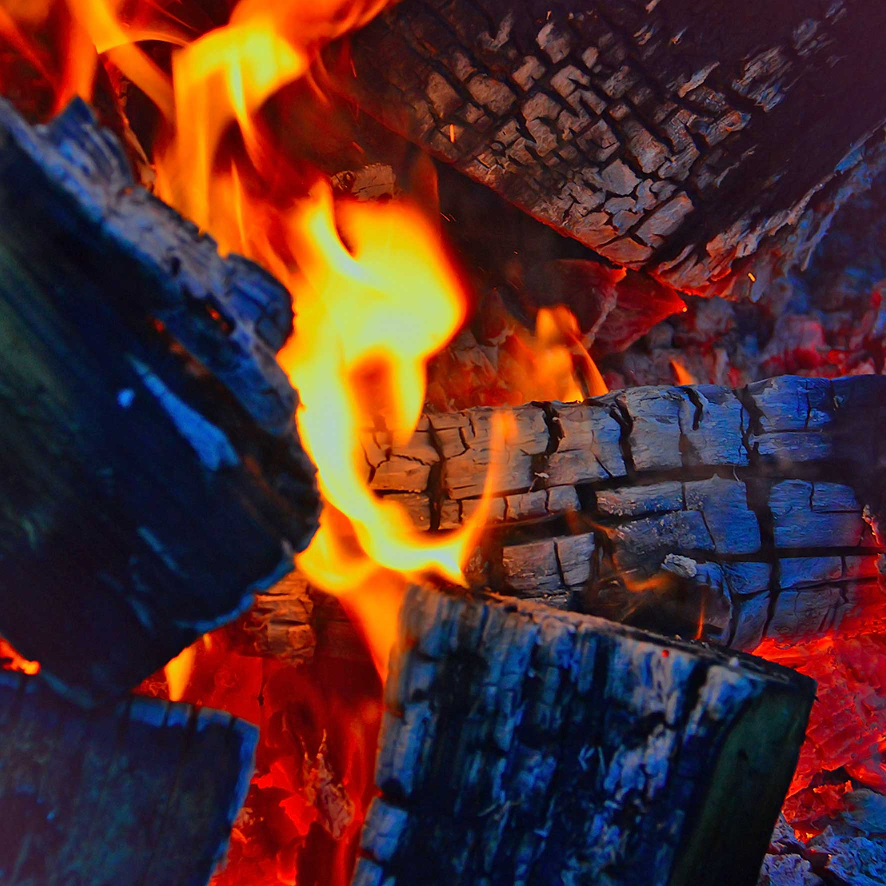 glowing firewood embers with small flame