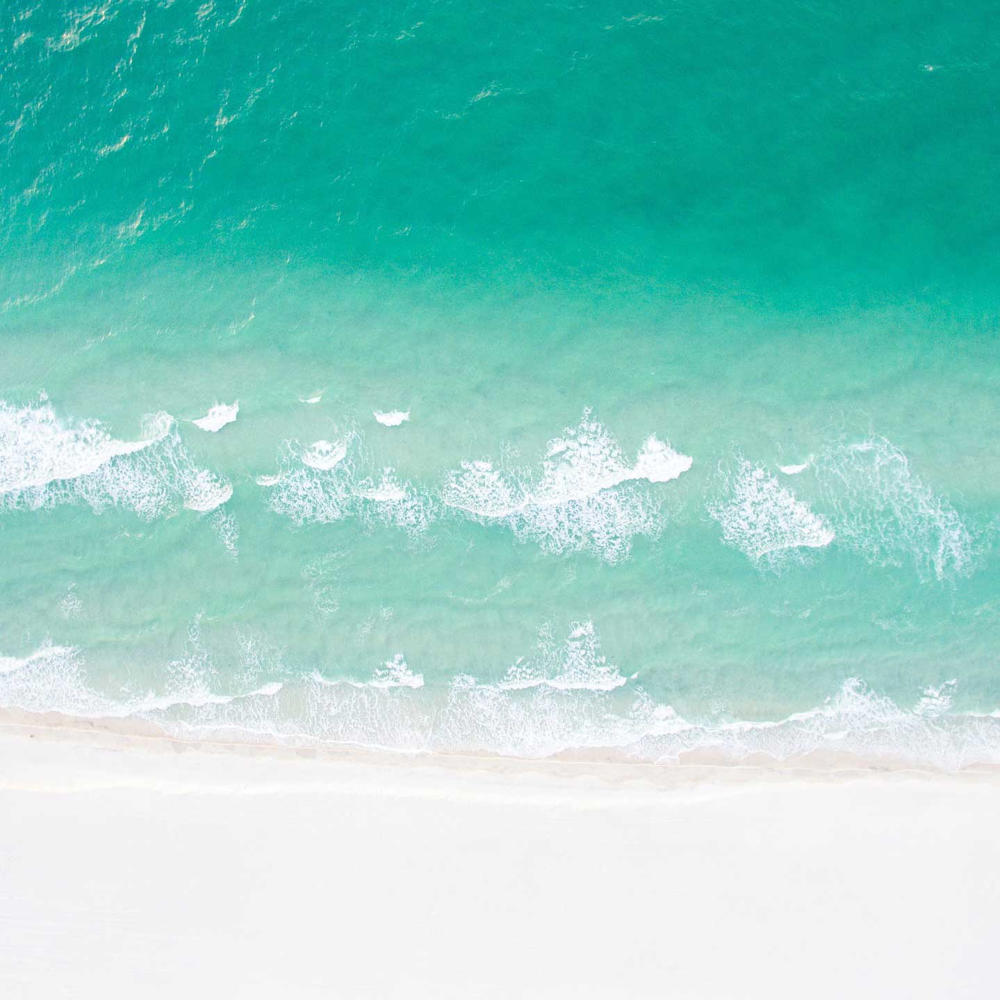 aerial of turquoise water and white sand beach