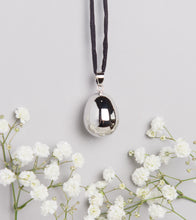 Load image into Gallery viewer, silver plated pebble Mexican bola pregnancy necklace on black hand dyed silk cord