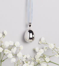 Load image into Gallery viewer, silver plated pebble shaped Mexican bola pregnancy necklace on light grey hand dyed silk cord