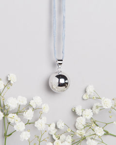 polished silver plated Mexican bola pregnancy necklace on light grey hand dyed silk cord