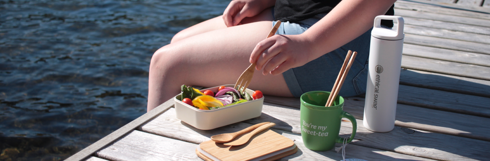 Girl sitting on the corner of a dock, eating salad from a Bamboo Food Container from Ethical Swag with a green mug and a stainless steel white water bottle on her side on a bright sunny day.