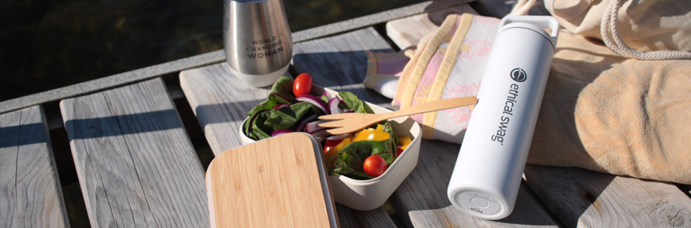 White Stainless Steel Water Bottle with Ethical Swag engraved on it. On the side is an open bamboo beige food container with salad inside. They are on a dock on a bright sunny day.