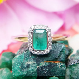 close up of emerald diamond cluster ring