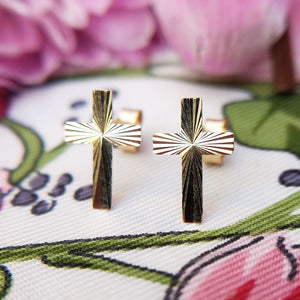 close up of solid gold cross studs