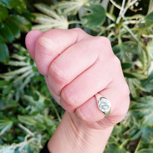 silver signet ring on woman's hand