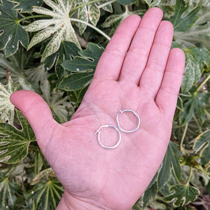 small silver hoops in hand for scale