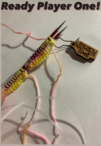 There is a white back ground with the words 'Ready Player One!' at the top.  There are a pair of knitting needles with yellow, purple and pink yarn being knitted on the needles.  There is a wood stitch marker that says 'ready knitter one'.