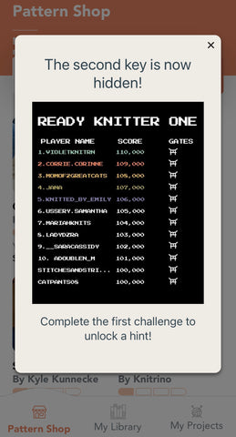 """An image of a black scoreboard that says """"Ready Knitter One"""" at the top.  There is a column for 'Player Name' , 'Score' and 'Gates'.  There is a list of names and scores below.  There is a white background and it says """"The second key is now hidden!"""" at the top and """"Complete the first challenge to unlock a hint!"""" below."""