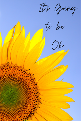 """A close up view of a yellow sunflower with a blue sky in the background.  In the top left it says """"It's going to be ok"""" in black cursive writing."""