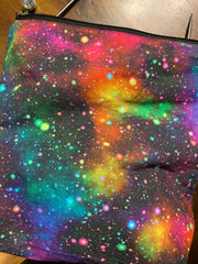 A small bag with a black zipper at the top.  There are two knitting needles sticking out the top.  The fabric looks like a rainbow galaxy.