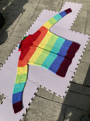 A cardigan in purple, periwinkle, mint, green, yellow, orange and red is laid out on pale purple drying mats out in the sun.