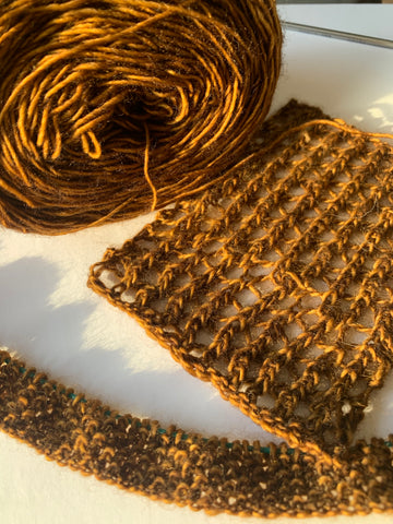 A bronze/gold yarn in a ball, a mesh gauge, and a seed stitch him are displayed on a white backdrop.