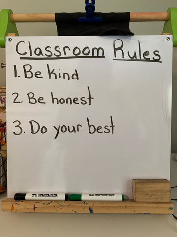 A white dry erase board that says Classroom Rules in black.  1.  Be kind 2.  Be honest 3.  Do your best