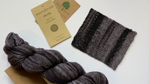 """An image of a variegated skein of yarn and a square swatch in dark and light grays on a white background.  There is a  yarn label that says """"monokrom fingering"""" and another brown rectangular label that says """"Knit One Plant One""""."""