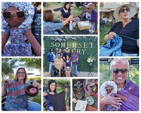 """A collage of photos.  Top left: a crochet doll with white fluffy hair, brown skin, sunglasses and a purple dress.  Top middle: a group of people knitting at a table.  Top right: a person in a navy blue t-shirt, white brimmed hat and sunglasses knitting a light blue garment.  Middle:  a group of people standing in front of a green wall that says """"Somerset Winery"""".  Bottom left: a person holding up a blue and pink knitted garment with the yarn in a bowl.  Bottom right: A person in a purple shawl and sunglasses holding a crochet doll of their likeness.  Bottom middle: a person holding up a gray knitted garment and a close up image of a table with a knitted swatch and a glass of wine."""