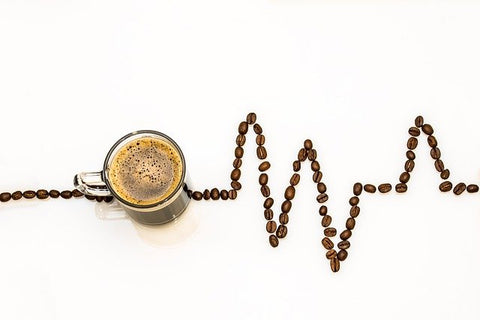 Coffee with a heart beat made of coffee beans.