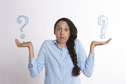 Woman shrugging shoulders with two question marks in her hands.