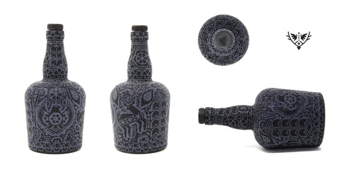 Botellas de Ron Dictador en colores negros intervenidas con arte huichol.