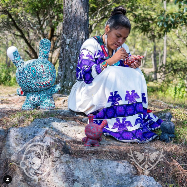 Huichol indigenous woman intervening with crystal bead pieces of KidRobot Dunny and Munny. In the background there are trees.