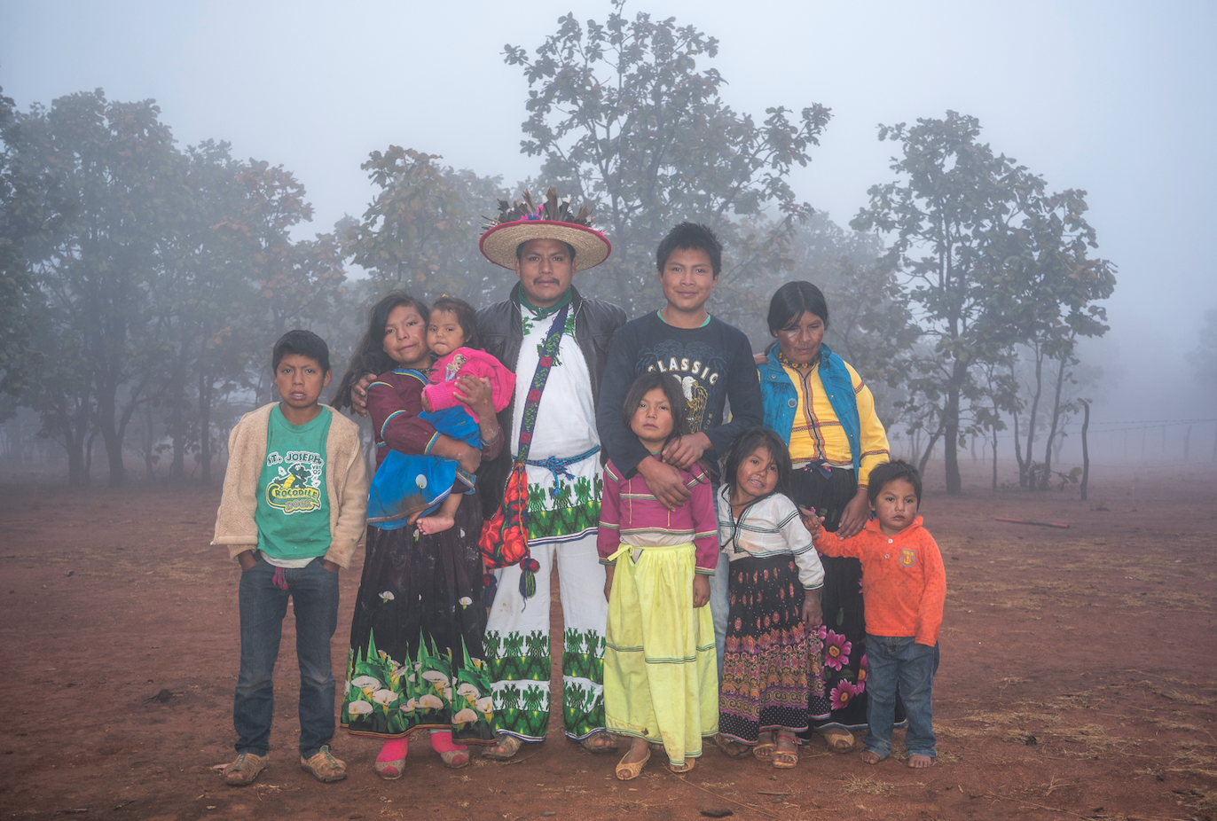 Huichol family with the mountains in the background in a hazy landscape.