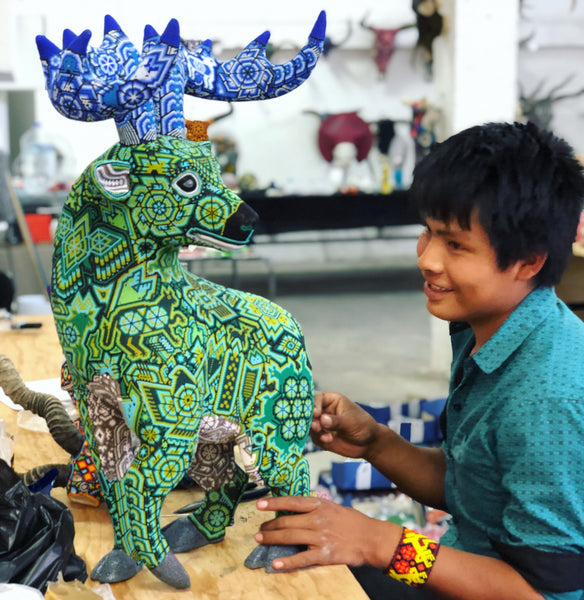 Huichol indigenous boy with a piece of green art representing a deer