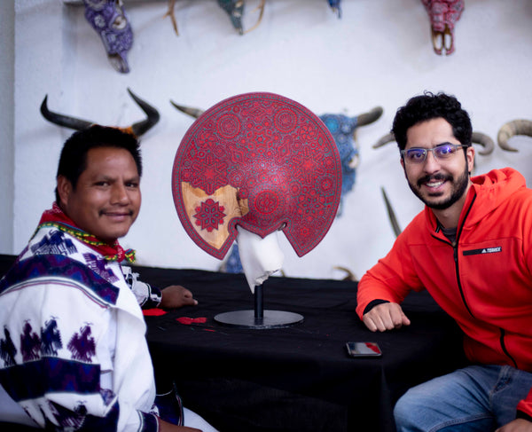 A Huichol artist and Fernando Motilla with a piece of art sculpture by Cesar Orrico intervened with Huichol art in red.