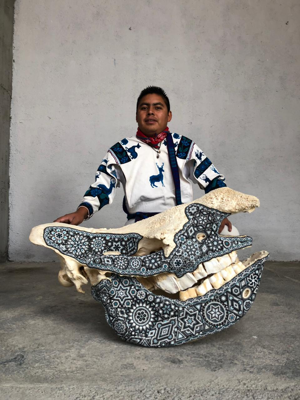 Rhinoceros skull intervened with crystal beads and the Huichol artist Sergio Bautista in the background